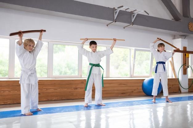 Twee jongens en een meisje in uniform voelen zich nieuwsgierig terwijl ze aikidobewegingen leren