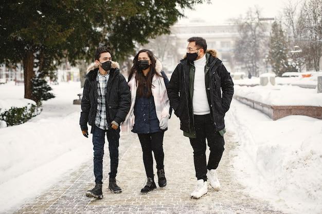 Twee jongens en een meisje met maskers. indiase vrienden op straat. jonge mensen in warme kleren.