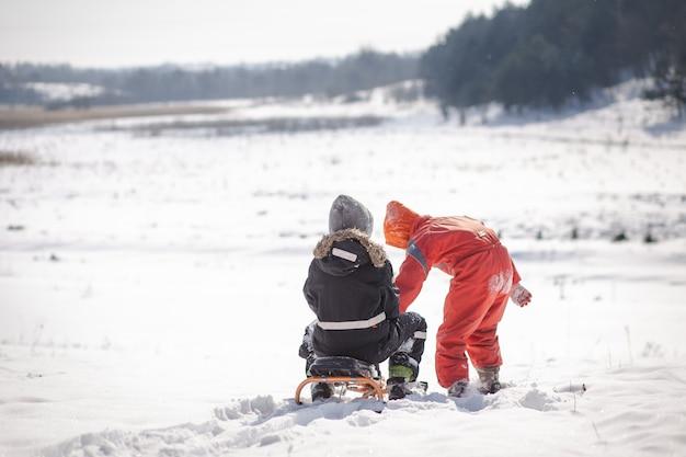 Twee jongens gaan van een hoge besneeuwde berg naar beneden. kinderen spelen in de winter in de sneeuw