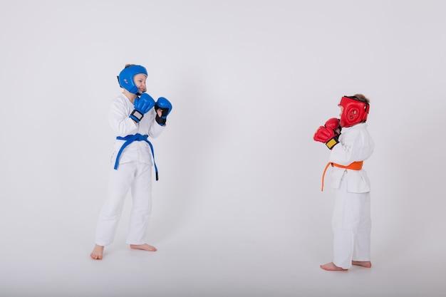 Twee jongens in een witte kimono, helm en handschoenen strijden op een witte achtergrond