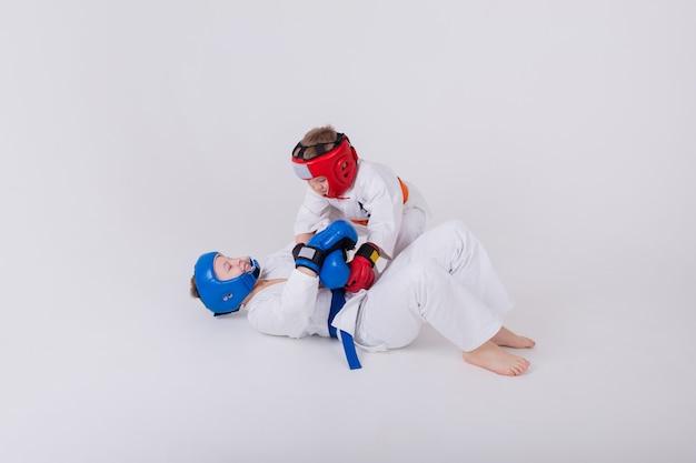 Twee jongens in een witte kimono, helm en handschoenen strijden tegen een witte achtergrond