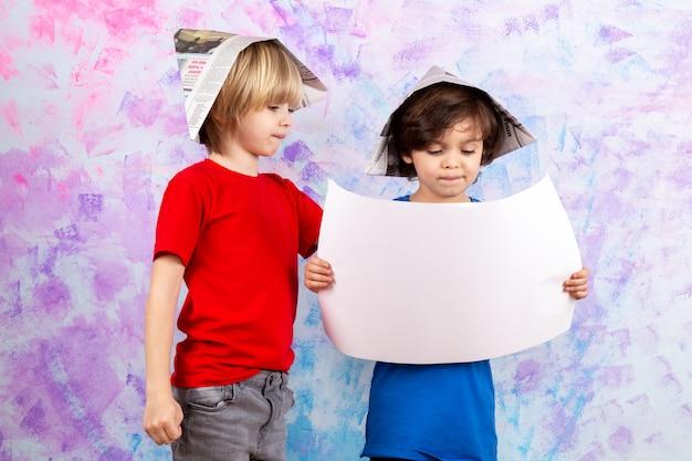 Twee jongens in rood en blauw t-shirt met papieren plannen op veelkleurige muur