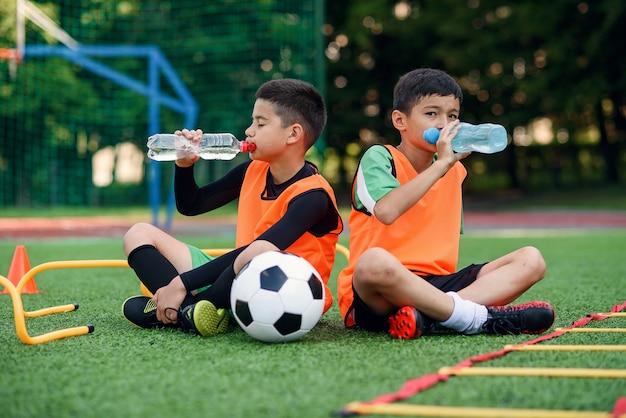 Twee jongens in voetbaluniformen die zoet water drinken.