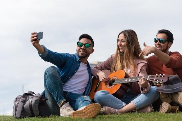 Twee jongens maken een foto met een vrouw met een gitaar