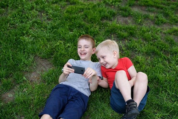 Twee jongens met een smartphone in hun handen met plezier op het gras
