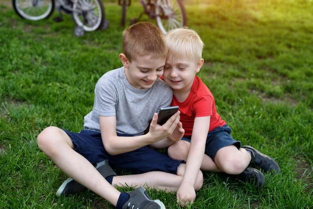 Twee jongens met een smartphone in hun handen zitten op het gras.