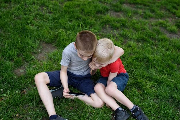 Twee jongens met een smartphone op het gras