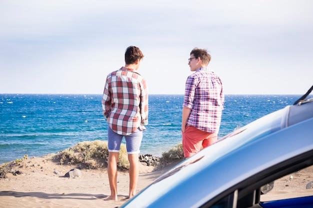 Twee jongens op het strand met auto die samen praten en plezier hebben voor de zee zonder golven - genieten en lifestyle concept voor reizigers