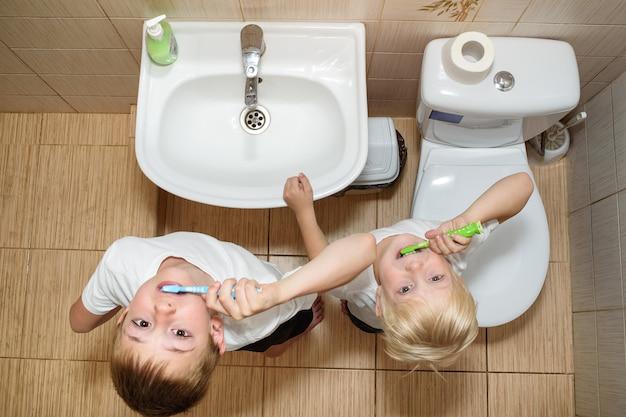 Twee jongens poetsen hun tanden in de badkamer