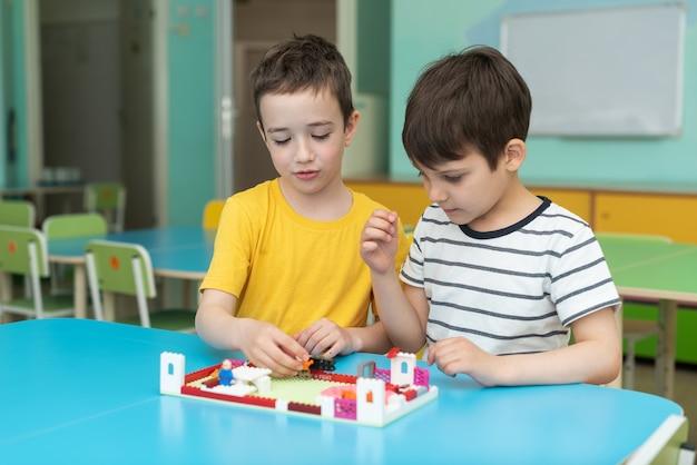 Twee jongens spelen enthousiast lego in de kleuterschool, vrije tijd op de kleuterschool