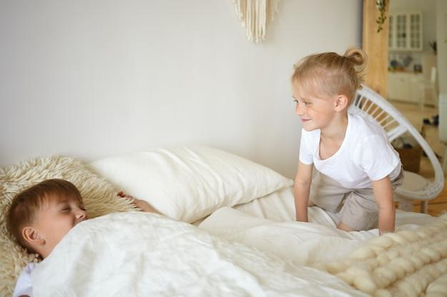 Twee jongens spelen in bed. schattige blonde kleine jongen zittend op witte bedkleren kijken naar zijn bejaarde broer die doet alsof hij slaapt. kinderen spelen in de slaapkamer. familie, jeugd en plezier