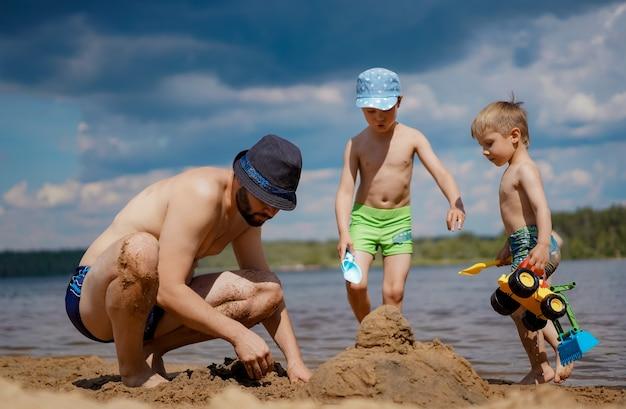Twee jongens spelen met vader op het strand en maken samen zandkasteel oudere jongen houdt een schop vast