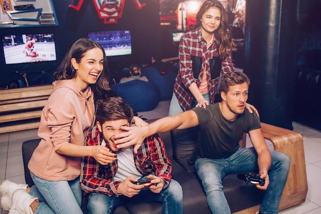 Twee jongens spelen spel op de bank in de kamer. een van hen houdt de hand voor het gezicht van de tegenstander. jonge vrouwen lachen. ze staan achter mannen.