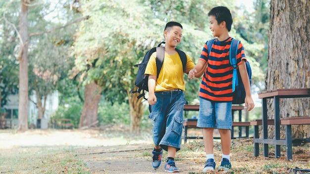 Twee jongens van de basisschool met schooltassen achter de rug.