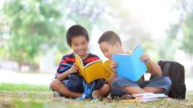 Twee jongens van primaire lezen en samen huiswerk maken.