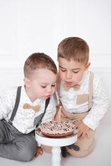 Twee jongens vieren verjaardag, kinderen hebben een b-day party. kinderen blazen kaarsjes op de verjaardagstaart. viering, wit minimalistisch interieur.