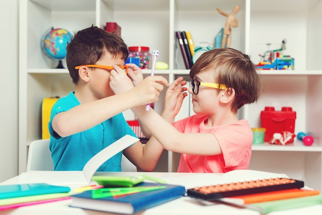Twee jongens zitten aan een bureau en hebben samen plezier. vrienden doen thuis huiswerk. thuisonderwijs concept. gelukkige brildragende kinderen houden na school voor de gek