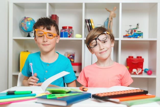 Twee jongens zitten aan een bureau en hebben samen plezier. vrienden doen thuis huiswerk.