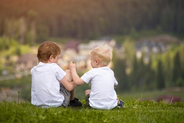 Twee jongens zitten op een heuvel en hebben plezier