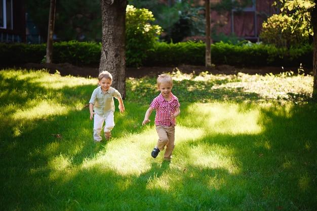 Twee jongensbroers die en in openlucht in een park spelen springen.