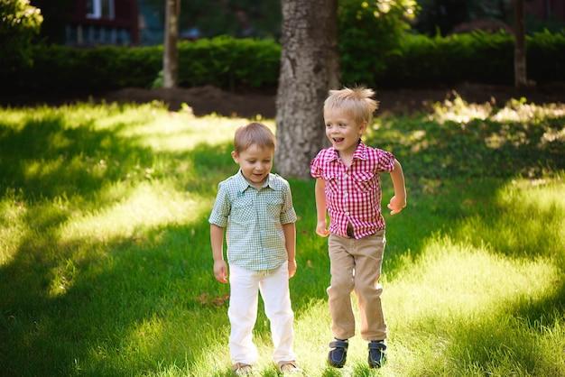 Twee jongensbroers spelen en springen buiten in een park.