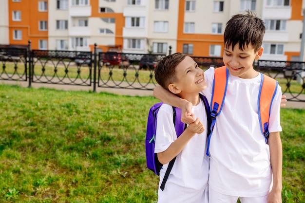 Twee jongensvriend schoolkinderen knuffelen elkaar op straat op weg naar school