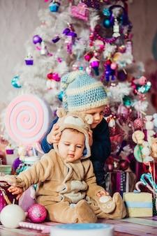 Twee jongetjes spelen met plezier voor een kerstboom