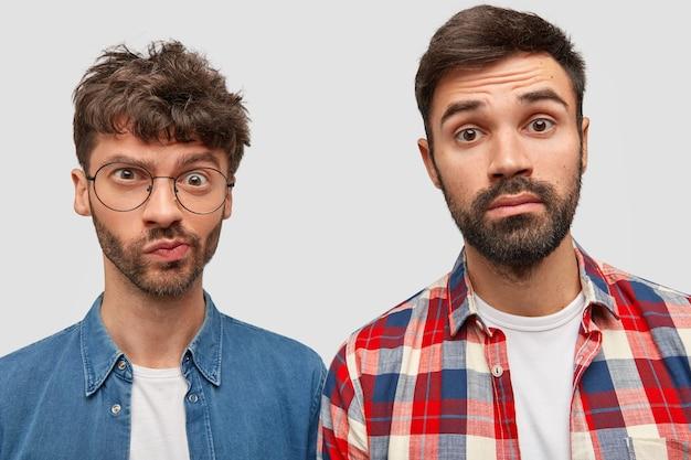 Twee journalisten met een bebaarde man hebben verwarde uitdrukkingen, werken aan het maken van een artikel, kijken met verbijstering naar de camera, gekleed in modieuze overhemden
