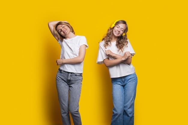 Twee juichende zussen luisteren naar muziek met een koptelefoon en dansen op een gele muur