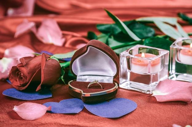 Twee kaarsen en een roos op een rode zijden achtergrond