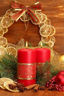 Twee kaarsen en kerstversiering, op houten achtergrond