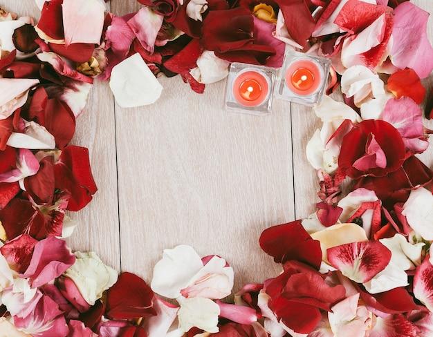 Twee kaarsen in een frame van rozenblaadjes op een houten ondergrond. foto met kopieerruimte