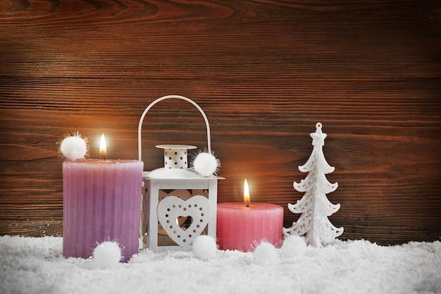 Twee kaarsen, lamp, dennenboom met sneeuwballen in een sneeuw over houten achtergrond, stilleven