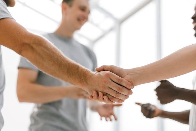 Twee kameraden die elkaar de hand schudden, staande in een kring van vrienden