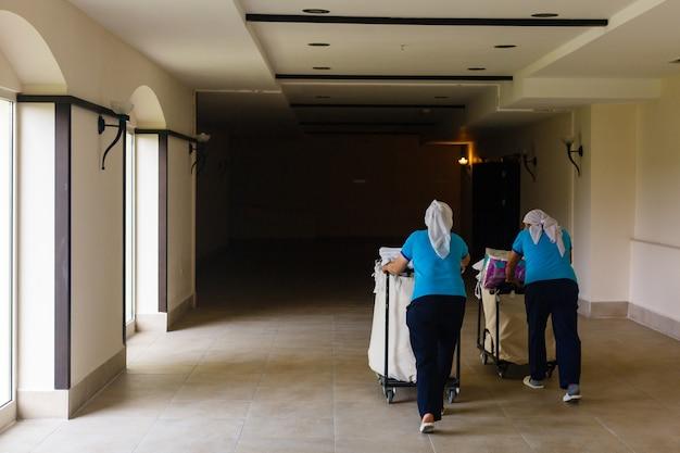 Twee kamermeisjesvrouwen die in een hotel schoonmaken.