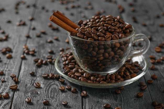 Twee kaneelstokjes in een kopje koffie bonen op een zwarte houten rustieke tafel.