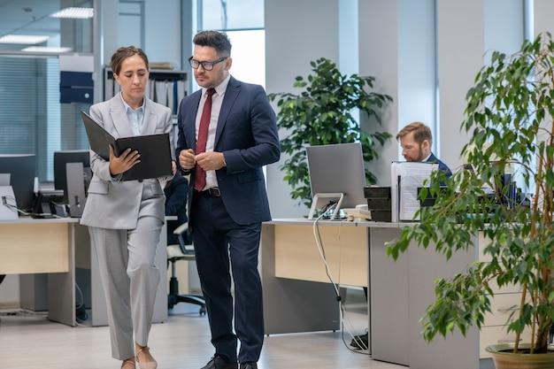 Twee kantoormedewerkers in pak bespreken contractvoorwaarden terwijl jonge vrouw map vasthoudt