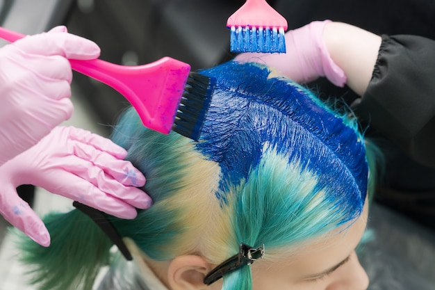 Twee kappers die roze borstel gebruiken terwijl ze blauwe verf aanbrengen op vrouwelijke cliënt met smaragdgroene haarkleur...