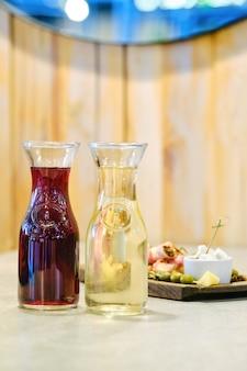 Twee karaffen met wijn en bord met snack