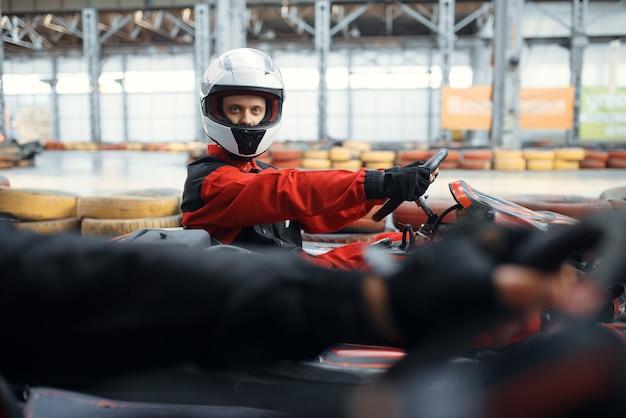 Twee kartracers vechten voor de overwinning op schoot, zijaanzicht, karting autosport binnen. snelheidsrace op nauwe karrenbaan met bandenbarrière. snelle voertuigcompetitie