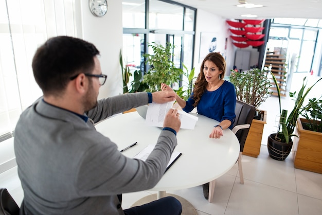 Twee kaukasische bedrijfsmensen die argument hebben tijdens vergadering