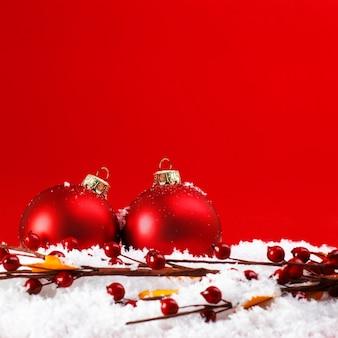 Twee kerstballen in de sneeuw met meidoorn, op rode achtergrond