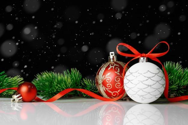 Twee kerstballen met fir tree op zwarte achtergrond