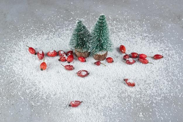 Twee kerstboombeeldjes en een bos heupen op kokospoeder op marmeren oppervlak