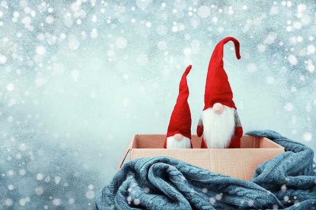 Twee kerstkabouters in open doos, gebreide deken