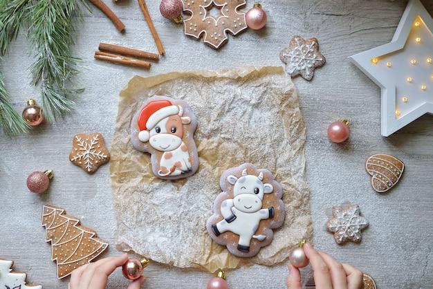 Twee kerstpeperkoeken in glazuur in de vorm van stieren, kerstsymbolen 2021, op een witte tafel met nieuwjaarsdecor, horizontaal.