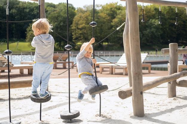 Twee kind jongens tweeling broers spelen op kinderspeelplaats in een zonnige herfstdag.