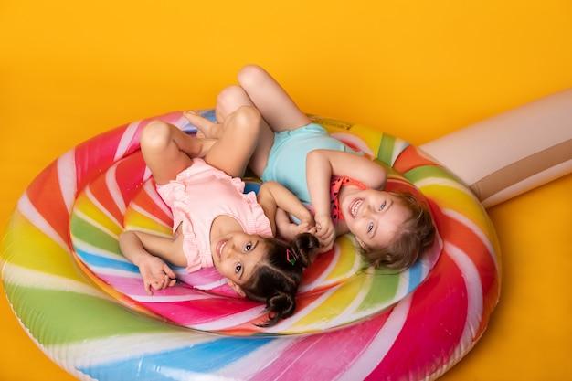 Twee kind meisje in zwempak liggend met plezier op kleurrijke opblaasbare matras lolly op gele achtergrond.