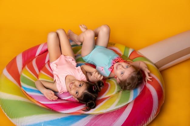 Twee kind meisje in zwempak liggend met plezier op kleurrijke opblaasbare matras lolly op gele ...