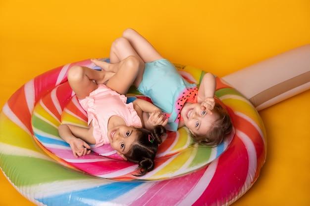Twee kind meisje in zwempak liggend met plezier op kleurrijke opblaasbare matras lolly.